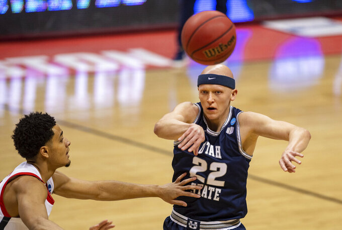 Utah State guard Brock Miller (22) passes the ball off to a teammate during the first half of a first round game against Texas Tech in the NCAA men's college basketball tournament, Friday, March 19, 2021, in Bloomington, Ind. (AP Photo/Doug McSchooler)