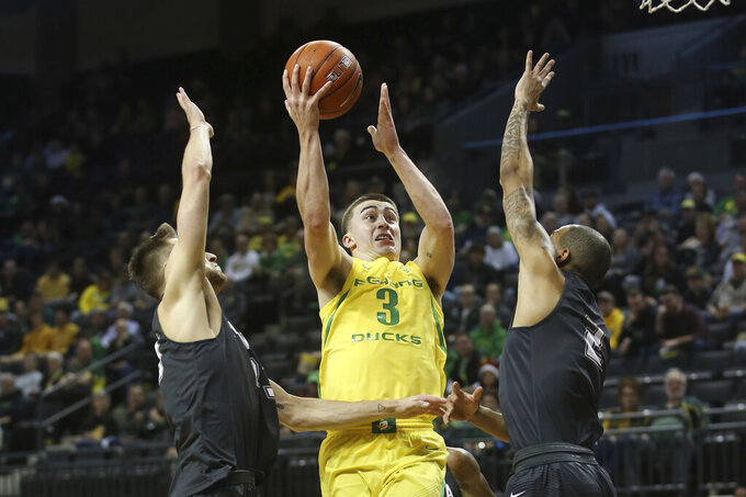Oregon's Payton Pritchard, center, shoots between Montana's Mack Anderson, left, and Kendal Manuel during the first half of an NCAA college basketball game in Eugene, Ore., Wednesday, Dec. 18, 2019. (AP Photo/Chris Pietsch)