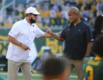 Kansas head coach Les Miles, left and Baylor head coach Dave Aranda, right, greet each other before start of an NCAA college football game in Waco, Texas, Saturday, Sept. 26, 2020. (Jerry Larson/Waco Tribune-Herald via AP)