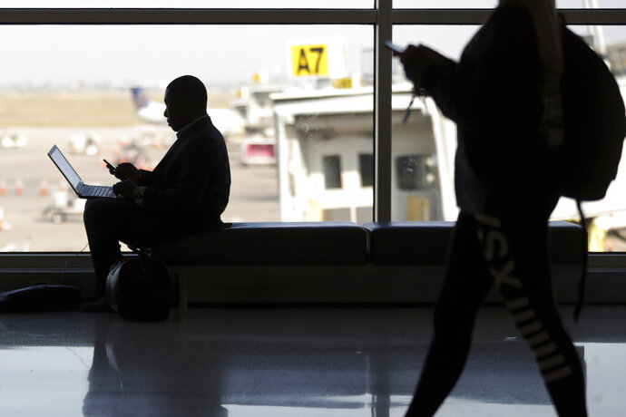 FILE - In this Wednesday, Nov. 21, 2018 file photo, travelers check their phones at Indianapolis International Airport in Indianapolis. On Tuesday, Nov. 12, 2019, a federal court in Boston ruled that warrantless U.S. government searches of the phones and laptops of international travelers at airports and other U.S. ports of entry violate the Fourth Amendment. (AP Photo/Michael Conroy)