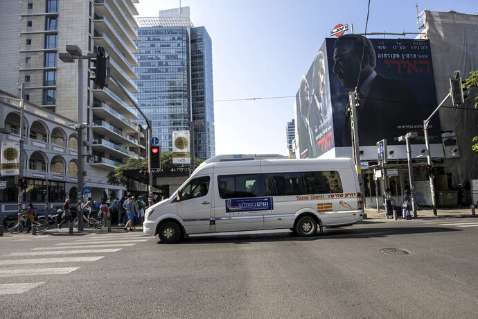 In this photo made on Saturday, Nov. 23, 2019, first ever public bus operated on Shabbat, drives through central Tel Aviv, Israel. Tel Aviv has taken a major step to cement its status as Israel's secular mecca, launching a public transit system operating on Saturdays and redrawing the lines in the Jewish state's culture wars between religious and secular citizens. (AP Photo/Tsafrir Abayov)