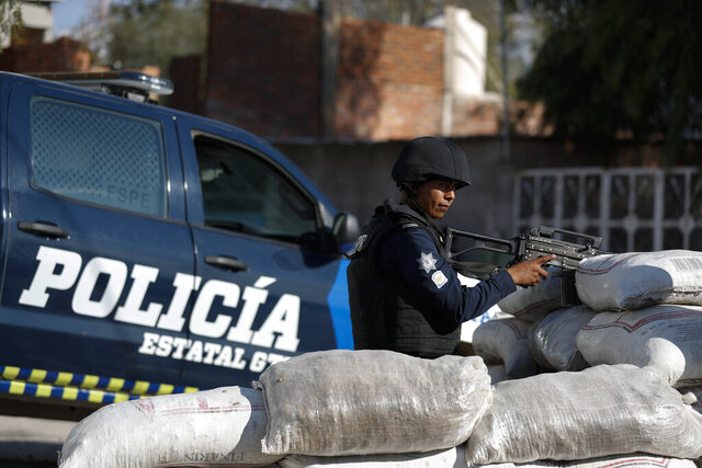 In this Feb. 12, 2020 photo, police stand guard behind a parapet of sandbags, at the entrance to Santa Rosa de Lima, birthplace of a local cartel that goes by the same name, in Guanajuato state, Mexico. Mexico's fastest-rising cartel, the Jalisco New Generation gang, has a reputation for ruthlessness and violence unlike any since the fall of the old Zetas cartel. In places like Guanajuato state it is fighting medieval-style battles for control of the state. (AP Photo/Rebecca Blackwell)
