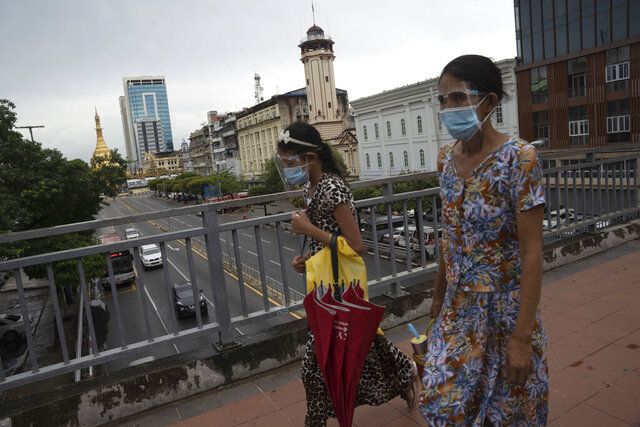 Pedestrians wearing face shields and masks walk at an overhead crossing at Sule Pagoda Road in Yangon, Myanmar,Monday, Sept. 21, 2020. Myanmar, faced with a rapidly rising number of coronavirus cases and deaths, has imposed the tightest restrictions so far to fight the spread of the disease in Yangon, the country's biggest city and main transportation hub. (AP Photo/Pyae Sone Win)
