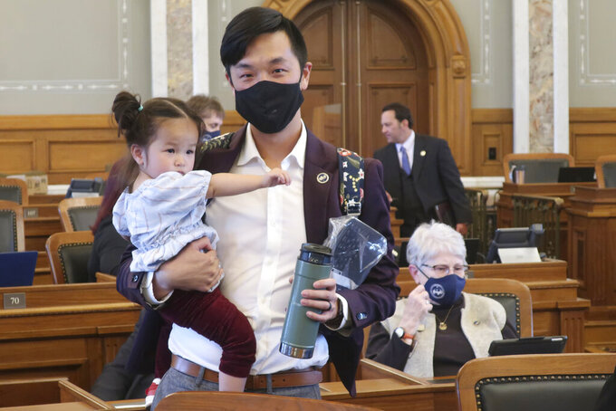 Kansas state Rep. Rui Xu, D-Westwood, holds his 18-month-old daughter, Astra, during a break in the House's work, Friday, May 7, 2021, at the Statehouse in Topeka, Kan. Lawmakers are working late as they tried to finish their business for the year. (AP Photo/John Hanna)