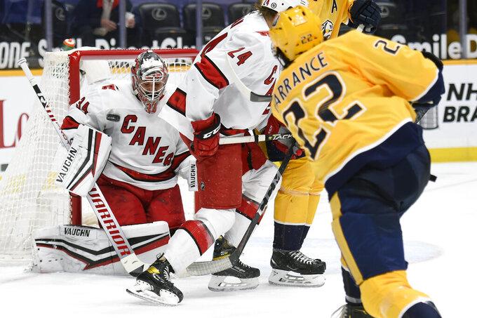 Carolina Hurricanes goaltender Petr Mrazek (34) blocks a shot by Nashville Predators defenseman David Farrance (22) during the second period of an NHL hockey game Monday, May 10, 2021, in Nashville, Tenn. (AP Photo/Mark Zaleski)