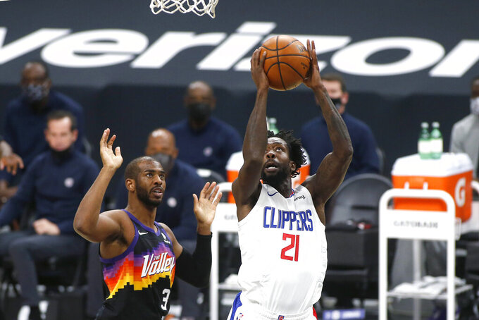 Los Angeles Clippers guard Patrick Beverley (21) shoots past the defense of Phoenix Suns guard Chris Paul (3) during the first half of an NBA basketball game Sunday, Jan. 3, 2021, in Phoenix. (AP Photo/Ralph Freso)