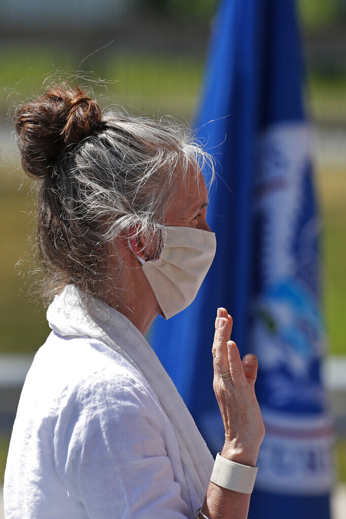 Tamara Sheen, originally from England, is sworn in as a new citizen outside the U.S. Citizenship and Immigration Services building, Thursday, June 4, 2020, in Lawrence, Mass. The federal agency is resuming services in many cities across the country after being shuttered for more than two months because of the coronavirus pandemic. (AP Photo/Elise Amendola)