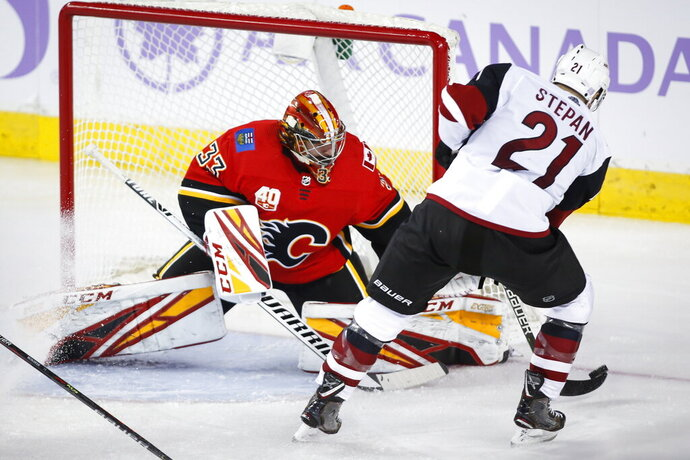 Arizona Coyotes' Derek Stepan, right, tries to get the puck past Calgary Flames goalie David Rittich during the third period of an NHL hockey game, Tuesday, Nov. 5, 2019 in Calgary, Alberta. (Jeff McIntosh/Canadian Press via AP)