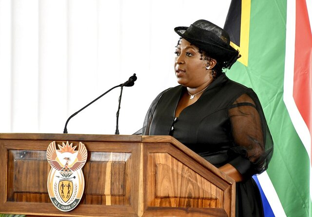 In this photo provided by the South African Government Communications and Information Services (GCIS), premier of the Mpumalanga province Refilwe Mtsweni-Tsipane addresses mourners, Sunday, Jan. 24, 2021, at the funeral of Cabinet minister Jackson Mthembu, who died of COVID-19 last week. Police are investigating Refilwe Mtsweni-Tsipane for failing to wear a mask and hugging a police officer at the public funeral. (Kopano Tlape/South African Government Communication and Information Services via AP)