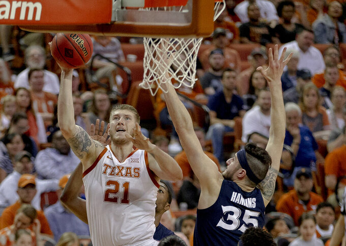 Texas forward Dylan Osetkowski (21) shoots next to Xavier forward Zach Hankins (35) during an NCAA college basketball game in the second round of the NIT on Sunday, March 24, 2019, in Austin, Texas. (Nick Wagner/Austin American-Statesman via AP)