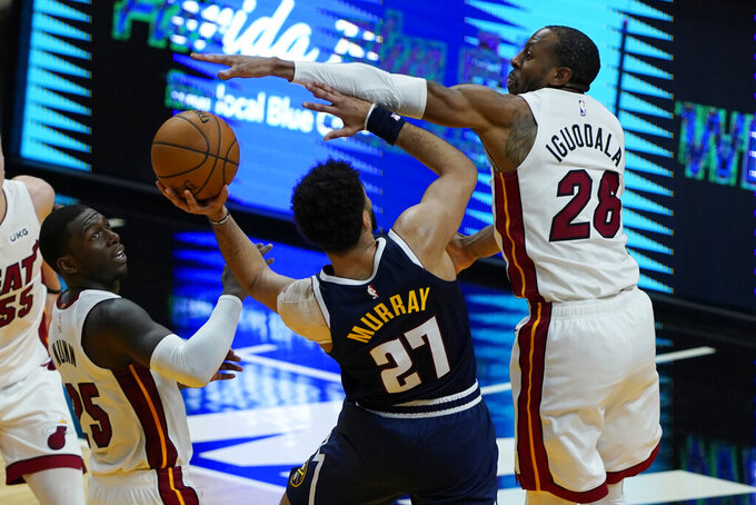 Miami Heat forward Andre Iguodala (28) blocks a drive to the basket by Denver Nuggets guard Jamal Murray (27) during the second half of an NBA basketball game, Wednesday, Jan. 27, 2021, in Miami. (AP Photo/Marta Lavandier)