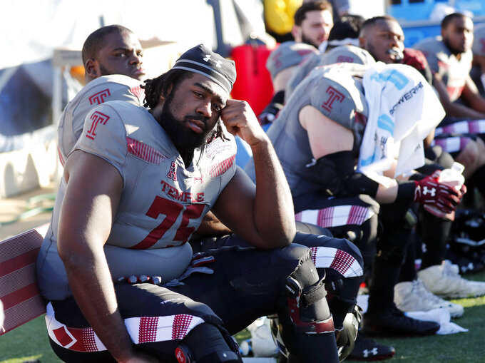 Temple offensive lineman Darian Bryant (75) and other players sit on the bench after the Independence Bowl NCAA college football game against Duke in Shreveport, La., Thursday, Dec. 27, 2018. (AP Photo/Rogelio V. Solis)