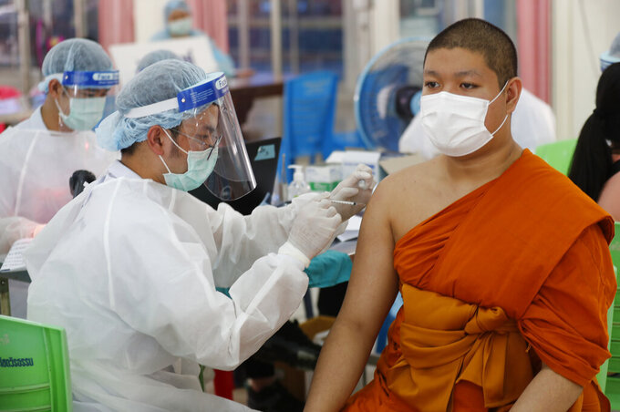 A health worker injects a Buddhist monk with dose of the Sinovac COVID-19 vaccine in Bangkok, Thailand, Monday, April 12, 2021. Thailand's Health Ministry warned Sunday that restrictions may need to be tightened to slow the spread of a fresh coronavirus wave, as the country hit a daily record for new cases. (AP Photo/Sakchai Lalit)