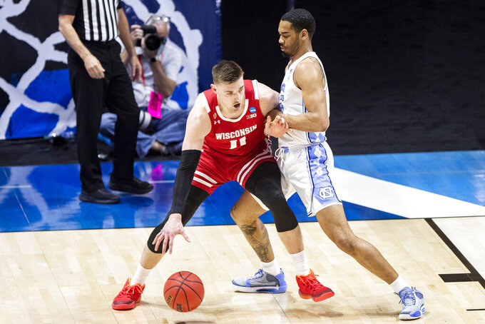 Wisconsin's Micah Potter (11) gets pressure from North Carolina's Garrison Brooks during the first half of a first-round game in the NCAA men's college basketball tournament, Friday, March 19, 2021, at Mackey Arena in West Lafayette, Ind. (AP Photo/Robert Franklin)