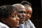 Andrew Ngwenya, center, and his wife, De-egma, right, and daughter sit outside their home in a working class township in Harare, the capital of Zimbabwe, on Monday, July, 12, 2021. Ngwenya and his wife went to a hospital that sometimes had spare doses, only to be turned away due to shortages with only a handful of people being inoculated. (AP Photo/Tsvangirayi Mukwazhi)
