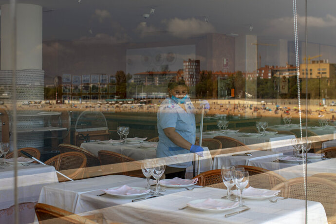 A woman cleans a restaurant prior to the opening, near the beach which is reflected in the glass, in Barcelona, Spain, Monday, June 29, 2020. Spain's foreign minister says that the European Union is putting together a list of 15 countries that are not bloc members and whose nationals will be allowed to visit from Wednesday. (AP Photo/Emilio Morenatti)