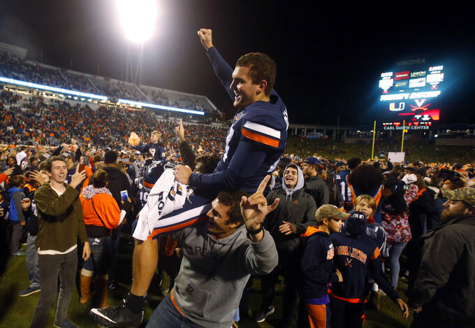 Virginia punter Lester Coleman (47) is lifted on to the shoulders of a fan as he celebrates his teams win over Miami after an NCAA college football game in Charlottesville, Va., Saturday, Oct. 13, 2018. Virginia defeated Miami 16-13. (AP Photo/Steve Helber)