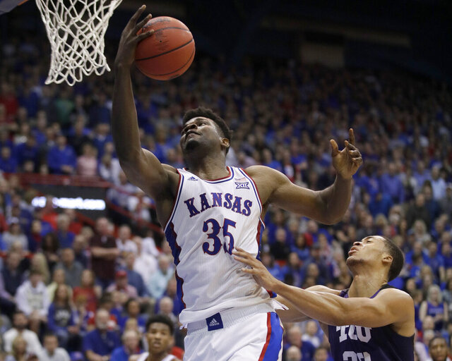 Kansas center Udoka Azubuike (35) gets past TCU forward Jaedon LeDee, right, for a basket during the first half of an NCAA college basketball game in Lawrence, Kan., Wednesday, March 4, 2020. (AP Photo/Orlin Wagner)