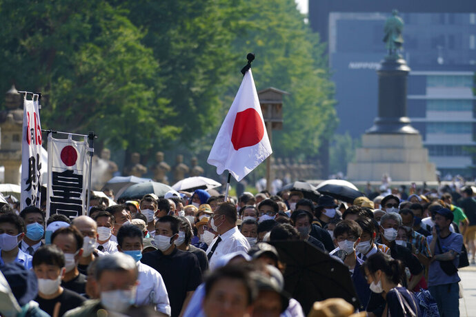 Worshippers queue to pay respects to the war dead at Yasukuni Shrine Saturday, Aug. 15, 2020, in Tokyo. Japan marked the 75th anniversary of the end of World War II. (AP Photo/Eugene Hoshiko)