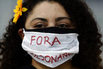 A demonstrator wears a mask with text written in Portuguese that reads
