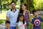 Patrick and Vicky Li Yip pose for a family photograph with their children, from left to right, Jesse, Kelsey and Toby, outside their home Friday, July 10, 2020, in Houston. Vicky Li Yip works from home and says online schooling has been exhausting, even with her husband helping out. But with her city becoming a national hot spot, she has been considering what it would mean for her children to face possible exposure every day. (AP Photo/David J. Phillip)