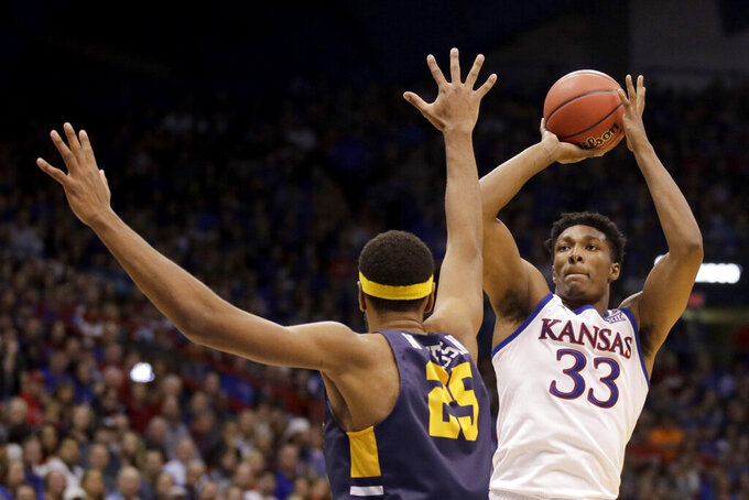 Kansas forward David McCormack (33) shoots over East Tennessee State center Lucas N'Guessan (25) during the first half of an NCAA college basketball game Tuesday, Nov. 19, 2019, in Lawrence, Kan. (AP Photo/Charlie Riedel)