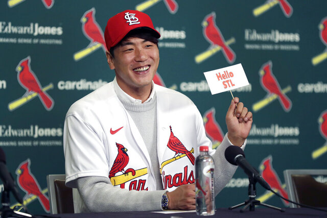 St. Louis Cardinals pitcher Kwang-Hyun Kim smiles as he holds up a sign during a news conference Tuesday, Dec. 17, 2019, in St. Louis. The Cardinals have signed the Korean left-hander to a two-year contract. (AP Photo/Jeff Roberson)