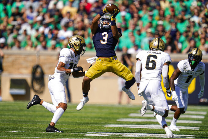 Notre Dame wide receiver Avery Davis (3) makes a catch between Purdue safety Cam Allen (10) and linebacker Jalen Graham (6) during the first half of an NCAA college football game in South Bend, Ind., Saturday, Sept. 18, 2021. (AP Photo/Michael Conroy)
