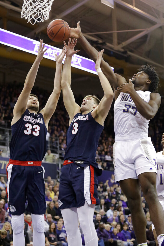 Gonzaga's Killian Tillie (33) and Filip Petrusev (3) reach for a rebound with Washington's Isaiah Stewart (33) in the first half of an NCAA college basketball game Sunday, Dec. 8, 2019, in Seattle. (AP Photo/Elaine Thompson)