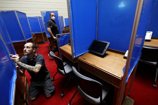 Worker Toby King, left, installs plastic partitions, with a removable blue protective covering, between desks, Monday, June 15, 2020, on the floor of the House Chamber at the Statehouse, in Providence, R.I. The partitions are being installed before the expected return of lawmakers to the Statehouse on Wednesday, June 17. (AP Photo/Steven Senne)