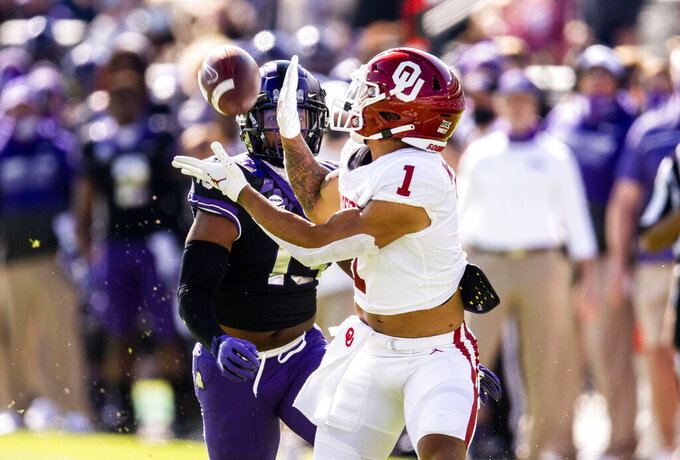 Oklahoma running back Seth McGowan (1) catches a pass as TCU linebacker Dee Winters (13) defends during the first half of an NCAA College football game, Saturday, Oct. 24, 2020, in Fort Worth, Texas. (AP Photo/Brandon Wade)