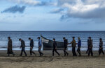 Migrants from Morocco walk along the shore escorted by Spanish Police after arriving at the coast of the Canary Island, crossing the Atlantic Ocean sailing on a wooden boat on Tuesday, Oct.20, 2020. Some 1,000 migrants have spent the night again sleeping in emergency tents in a dock while authorities in the Canary Islands complain that the Spanish government keeps blocking transfers of newly arrived migrants to the mainland over coronavirus concerns. (AP Photo/Javier Bauluz)