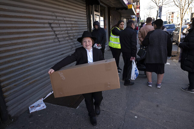 FILE - In this Thursday, March 26, 2020 file photo, a boy carries a box of matzos for Passover that he picked up from his synagogue in the Brooklyn borough of New York. The coronavirus has forced Jewish families to limit the celebratory Passover meals known as seders from extended families and friends to small, one-household affairs. (AP Photo/Mark Lennihan)