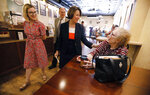 FILE - In this May 25, 2019, file photo, Democratic presidential candidate Sen. Amy Klobuchar, D-Minn., center, and her daughter Abigail, left, talks with Linda Gehrke, of Iowa Falls, right, during a meet and greet at a coffee shop in Iowa Falls, Iowa. (AP Photo/Charlie Neibergall, File)