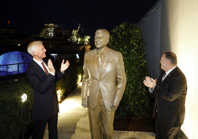 Together with United States Ambassador in Germany Richard Grenell, right, and Fred Ryan Board Chairman of the Reagan Foundation, left, Secretary of State Mike Pompeo unveils a statue of former President Ronald Reagan on the top of United States embassy in Berlin, Germany, Friday, Nov. 7, 2019. AP Photo/Markus Schreiber)