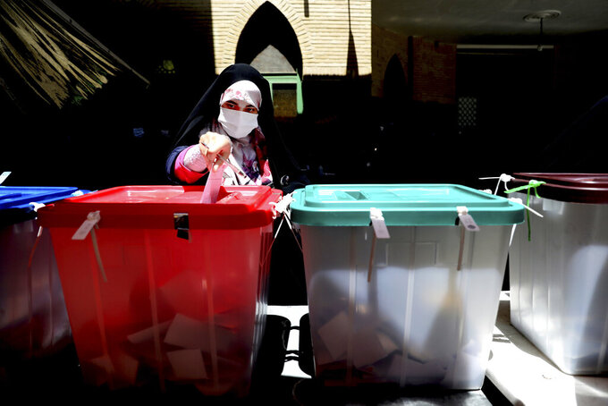 A voter casts her ballot for the presidential election at a polling station in Tehran, Iran, Friday, June 18, 2021. Iranians voted Friday in a presidential election that a hard-line protege of Supreme Leader Ayatollah Ali Khamenei seemed likely to win, leading to low turnout fueled by apathy and calls for a boycott. (AP Photo/Ebrahim Noroozi)