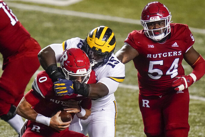 Michigan's Christopher Hinton (15) gets past Rutgers offensive lineman Cedrice Paillant (54) to sack quarterback Noah Vedral (0) during the first half of an NCAA college football game Saturday, Nov. 21, 2020, in Piscataway, N.J. (AP Photo/Frank Franklin II)
