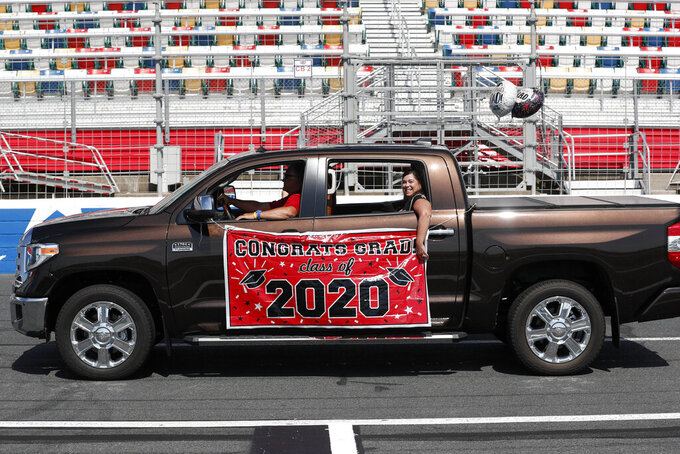 Class of 2020 graduates from Cabarrus Early College of Technology drive on the Charlotte Motor Speedway to receive their diplomas during a graduation event in Concord, N.C., Friday, June 12, 2020.  Due to the coronavirus pandemic Cabarrus County schools participated in a first-of-its-kind commencement ceremony for students and family. (AP Photo/Gerry Broome)
