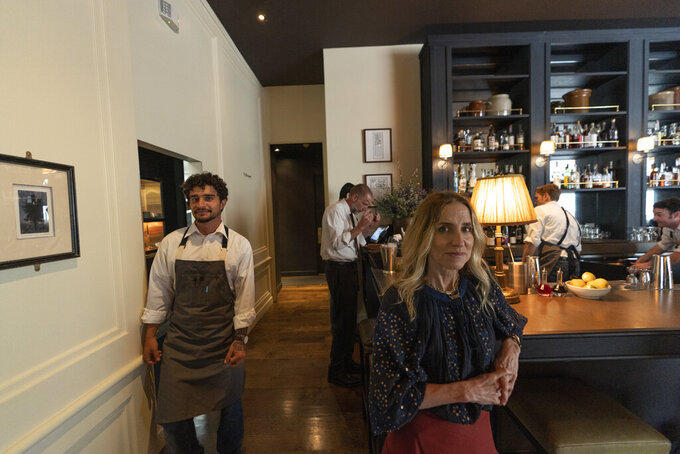 In this Saturday, June 19, 2021, photo, Caroline Styne, owner and wine director at The Lucques Group, right, poses for a picture at the A.O.C. Brentwood restaurant's bar in Los Angeles. Styne has turned away dozens of customers at the company's A.O.C. West Hollywood restaurant because she doesn't have the staff to serve them, leaving seats empty. (AP Photo/Damian Dovarganes)