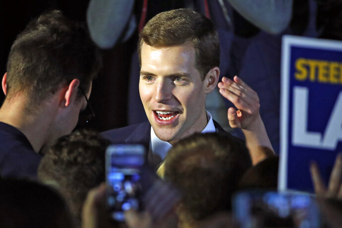 Conor Lamb, the Democratic candidate for the March 13 special election in Pennsylvania's 18th Congressional District, center, celebrates with his supporters at his election night party in Canonsburg, Pa., early Wednesday, March 14, 2018. A razor's edge separated Lamb and Republican Rick Saccone early Wednesday in their closely watched special election in Pennsylvania, where a surprisingly strong bid by first-time candidate Lamb severely tested Donald Trump's sway in a GOP stronghold. (AP Photo/Gene J. Puskar)
