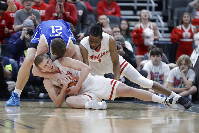 IBradley's Nate Kennell keeps hold of the ball as Drake's Liam Robbins (21) tries to pull it away an Bradley's Ari Boya, right, watches during the first half of an NCAA college basketball game in the semifinal round of the Missouri Valley Conference men's tournament Saturday, March 7, 2020, in St. Louis. (AP Photo/Jeff Roberson)