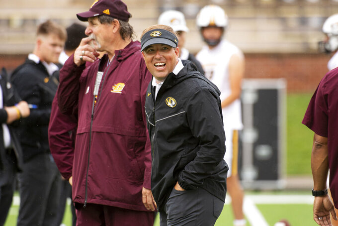 Missouri head coach Eliah Drinkwitz laughs with the Central Michigan coaching staff before the start of an NCAA college football game, Saturday, Sept. 4, 2021, in Columbia, Mo. (AP Photo/L.G. Patterson)
