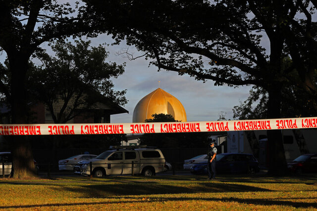 FILE - In this March 17, 2019, file photo, a police officer stands guard in front of the Masjid Al Noor mosque in Christchurch, New Zealand, where one of two mass shootings occurred. A comprehensive report released Tuesday, Dec. 8, 2020 into the 2019 Christchurch mosque shootings in which 51 Muslim worshippers were slaughtered sheds new light on how the gunman was able to elude detection by authorities as he planned out his attack. (AP Photo/Vincent Yu, File)