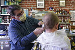 Mike Douglass, left, gives Kent Kjestrom a haircut at East J Barbers in Sacramento, Calif., Thursday, Jan. 21, 2021. Local officials and businesses in the 13-county Greater Sacramento region were caught off guard last week when outdoor dining and worship services were OK again, hair and nail salons and other businesses could reopen, and retailers could allow more shoppers inside. It's still a mystery how the state made the decision or how and when it will lift the most serious restrictions on the bulk of the state's population because officials won't share their data. (AP Photo/Rich Pedroncelli)