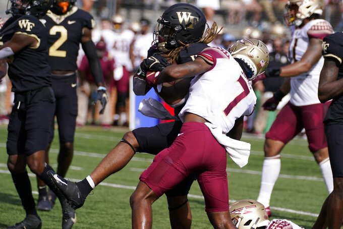 Wake Forest running back Christian Beal-Smith, center left, scores past Florida State defensive back Jarrian Jones (7) during the first half of an NCAA college football game Saturday, Sept. 18, 2021, in Winston-Salem, N.C. (AP Photo/Chris Carlson)