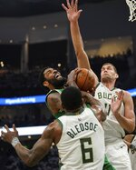 Boston Celtics' Kyrie Irving tries to shoot between Milwaukee Bucks' Eric Bledsoe and Brook Lopez during the second half of Game 2 of a second round NBA basketball playoff series Tuesday, April 30, 2019, in Milwaukee. The Bucks won 123-102 to tie the series at 1-1. (AP Photo/Morry Gash)