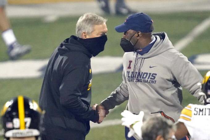 Iowa head coach Kirk Ferentz, left, and Illinois head coach Lovie Smith shakes hands after an NCAA college football game Saturday, Dec. 5, 2020, in Champaign, Ill. Iowa won 35-21. (AP Photo/Charles Rex Arbogast)
