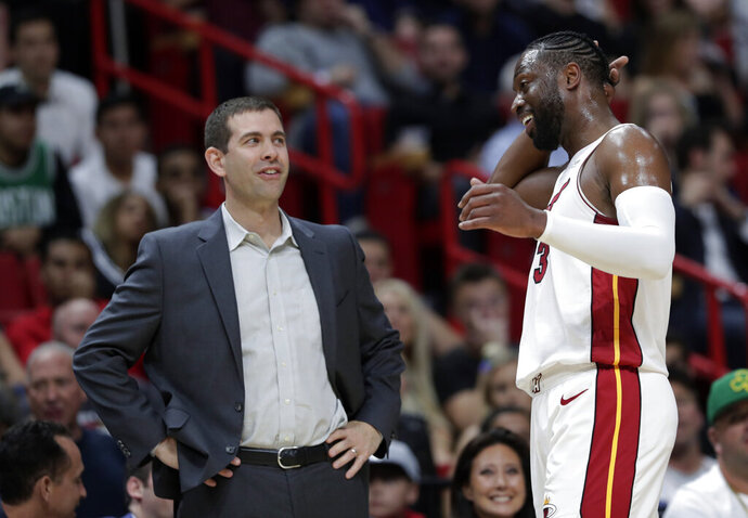 Boston Celtics coach Brad Stevens, left, talks with Miami Heat guard Dwyane Wade during the second half of an NBA basketball game Wednesday, April 3, 2019, in Miami. The Celtics won 112-102. (AP Photo/Lynne Sladky)
