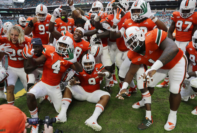 Miami defensive back Trajan Bandy, center, poses with his teammates after recovering a fumble by Pittsburgh during the first half of an NCAA college football game, Saturday, Nov. 24, 2018, in Miami Gardens, Fla. (AP Photo/Lynne Sladky)