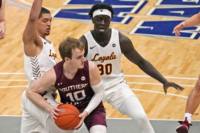 Southern Illinois' Ben Harvey (10) looks to pass as Loyola of Chicago's Lucas Williamson, left, and Aher Uguak (30) defend during the first half of an NCAA college basketball game in the quarterfinal round of the Missouri Valley Conference men's tournament Friday, March 5, 2021, in St. Louis. (AP Photo/Jeff Roberson)